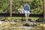 Mother and daughter sitting on wooden bridge, girl throwing stone into mountain stream - DIGF04731