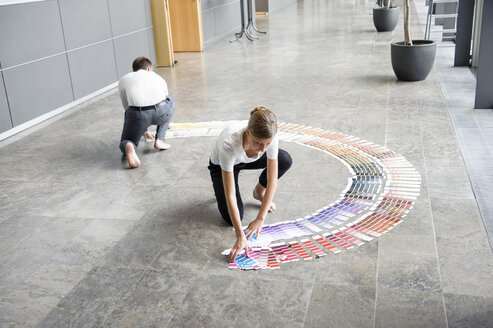 Young woman and mid adult man arranging swatches on lobby floor - CUF43794
