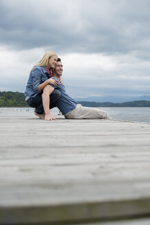 A man and woman sitting close together on a jetty by a lake. - MINF04928