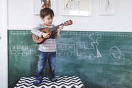 A child standing in front of a blackboard holding a ukulele. - MINF05009