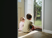 A child, boy and a toddler, girl looking out of a screen door, brother and sister. - MINF05039
