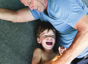 A boy, child lying next to man, father, hugging and laughing. - MINF05042