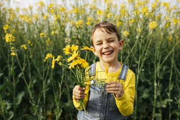 Portrait of little boy with picked yellow flowers in nature - JRFF01777