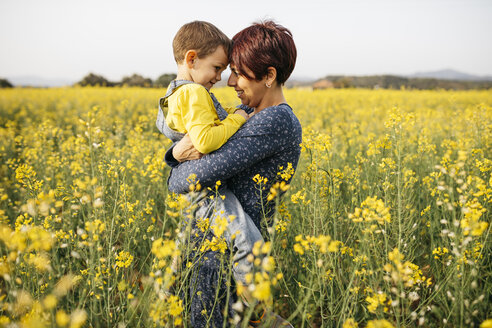 Mother standing with her little son in a rape field - JRFF01792