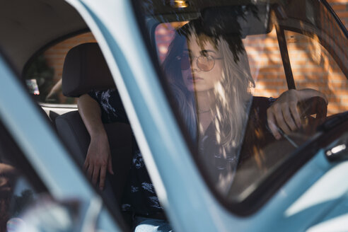 Young woman wearing sunglasses sitting in a car - KKAF01348