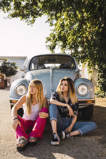 Two young women sitting outside at a vintage car - KKAF01363