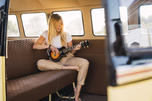 Young woman sitting in a van playing guitar - KKAF01366