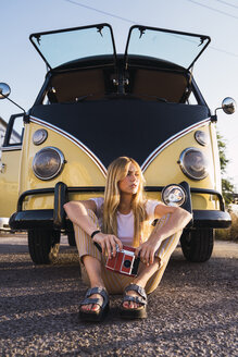 Young woman holding vintage camera sitting outside at a van - KKAF01375