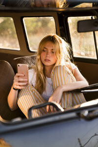 Young woman sitting in a van using cell phone - KKAF01390