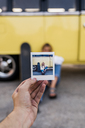 Hand holding instant photo of young woman with skateboard sitting at a van - KKAF01396