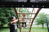 Bearded man wearing baseball cap helping young girl climbing up a ladder of a climbing frame on a playground. - MINF05075