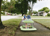 A girl, toddler, walking through a suburban neighbourhood using a walking frame. - MINF05099