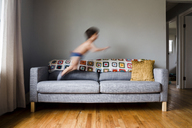 Boy, child jumping on a sofa in a living room. - MINF05138
