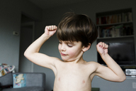 Boy, child flexing arm muscles in a living room. - MINF05144