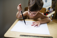 High angle view of young boy with brown hair sitting at a table, holding pen, drawing. - MINF05179