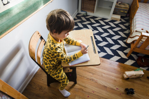 High angle view of young boy with brown hair wearing yellow pyjamas sitting at a table in a nursery, writing into notebook. - MINF05200