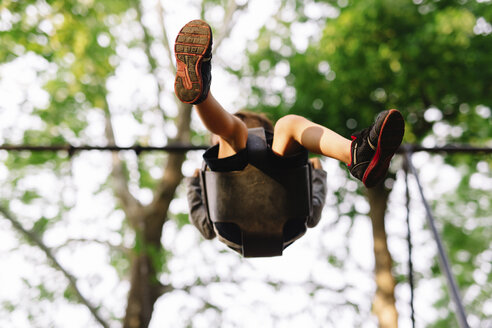 Low angle view of boy sitting on a swing underneath a tree. - MINF05215