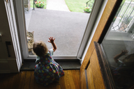 High angle rear view of young girl kneeling at a front door, touching glass. - MINF05218