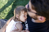 High angle view of bearded man sitting outdoors, holding sleeping young girl. - MINF05224
