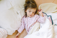 High angle view of young girl wearing pink pyjamas lying on her back in a bed, sleeping. - MINF05236