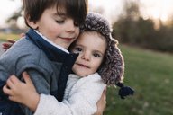 Close up of young boy with brown hair and young girl wearing furry hat standing outdoors, hugging. - MINF05242