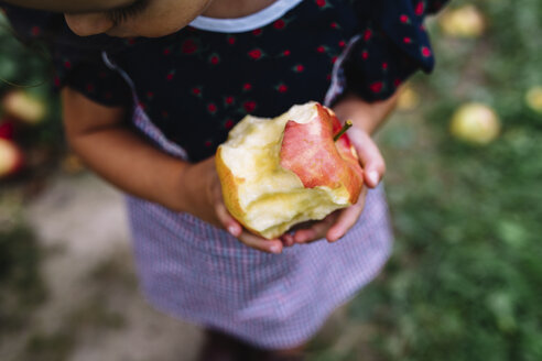 High angle close up of girl standing outdoors, holding half-eaten apple. - MINF05248