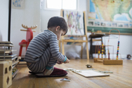 Boy, child, crouching on floor of a playroom playing with a puzzle. - MINF05266