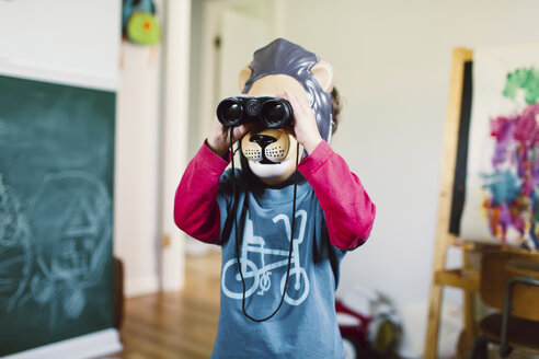 Young boy wearing lion mask standing indoors, looking through a pair of binoculars. - MINF05278