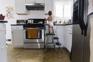 Rear view of young girl wearing nappy standing on a stool in a kitchen. - MINF05293