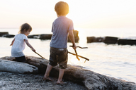 Young boy and girl playing on a beach by the ocean, holding sticks. - MINF05299