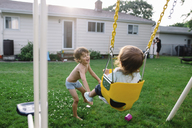 Young bare chested boy with brown hair standing in a garden, pushing young girl sitting on a swing. - MINF05305