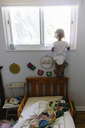 Rear view of young girl standing on the headboard of a bed in a nursery, looking out of window. - MINF05317