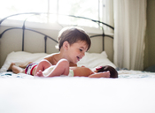 Young boy with brown hair and small baby lying on a bed. - MINF05380