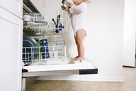 Young girl wearing onesie standing on the open door of a dishwasher in a kitchen. - MINF05398