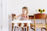 Young girl wearing dress sitting in a high chair, eating. - MINF05416