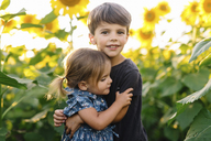 Young boy with brown hair and young girl standing in sunflower field, smiling and hugging. - MINF05422