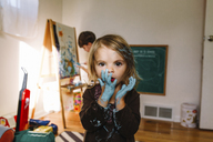 Young girl holding her hands, covered in blue paint, in front of her mouth, young boy drawing at an easel in background. - MINF05425