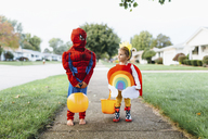 Young girl standing on a pavement, wearing colourful costume with rainbow, sun and clouds, looking at boy wearing Spiderman costume standing beside her. - MINF05428