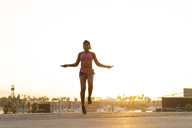 Spain, Barcelona, young black woman skipping rope at sunrise - AFVF01274