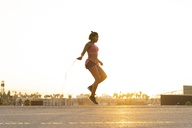 Spain, Barcelona, young black woman skipping rope at sunrise - AFVF01277