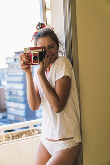 Portrait of happy young woman standing at the window taking picture with old-fashioned camera - KKAF01424