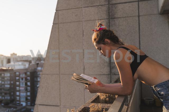 Young woman wearing bra reading book on balcony - KKAF01430