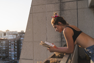 Young woman wearing bra reading book on balcony - KKAF01430