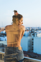 Rear view of topless young woman standing on balcony - KKAF01436