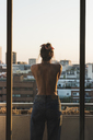 Rear view of topless young woman standing on balcony - KKAF01439