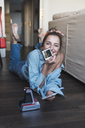 Portrait of happy young woman lying on the floor with instant photos of herself - KKAF01445
