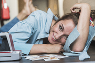 Portrait of happy young woman lying on the floor with instant photos - KKAF01448