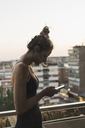 Young woman wearing black dress using cell phone on balcony - KKAF01451