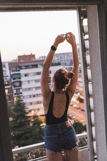 Rear view of young woman standing on balcony - KKAF01454