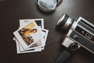 Stack of instant photos of young woman next to camera - KKAF01460